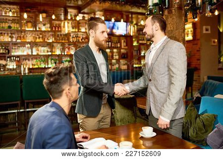 Bearded Young Entrepreneur In Formalwear Shaking Hand Of His Business Partner After Successful Compl