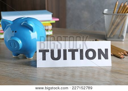 Paper with word TUITION and piggy bank on table