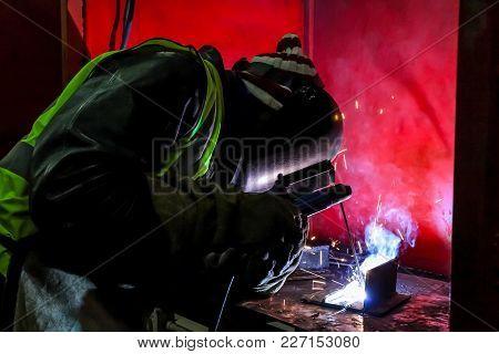 Man Welding Metal In A Workshop, Tradesman Working With Welding Torch