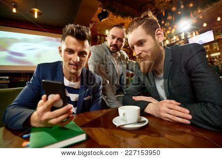 Group Of Friends Watching Funny Video On Smartphone And Enjoying Fragrant Coffee While Gathered Toge