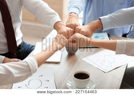 Young people in office wear putting hands together indoors. Unity concept