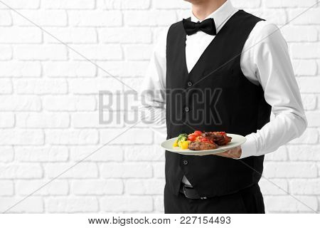 Waiter holding plate with meat and vegetables on brick wall background