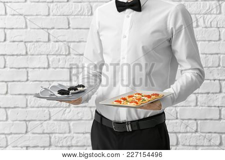 Waiter holding plate with appetizers on brick wall background
