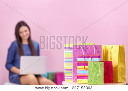 Colorful shopping bags and blurred woman with laptop on background. Online shopping concept