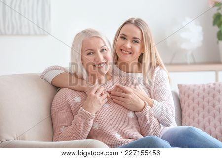 Young daughter and mother sitting on sofa at home