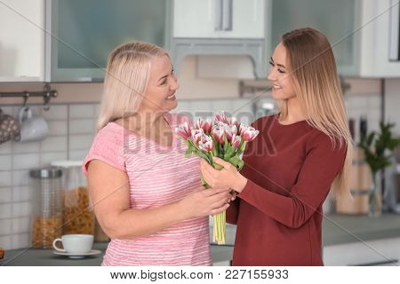Young daughter and mother with bouquet of flowers at home