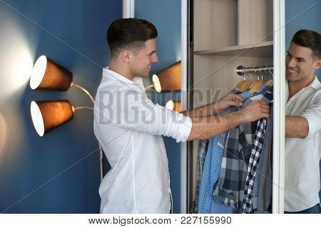 Man picking shirt from closet. Fashionable wardrobe