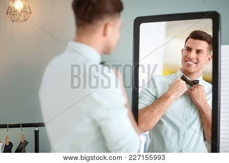Man in new outfit looking at himself in mirror indoors. Fashionable wardrobe