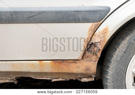 Damaged White Car With Scratched Paint And Rust With Holes At The Bottom Of The Floor Close Up