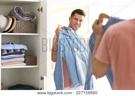 Man with new shirt looking at himself in mirror indoors. Fashionable wardrobe