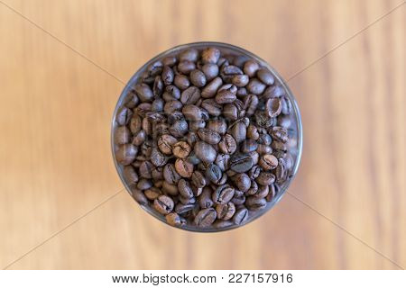 A Grain Of Coffee In A Glass On A Blurred Background. View From Above