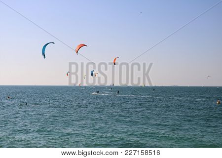 Kite Surfing On A Beach In Dubai The People On A Surfboard Among The Ocean Waves.