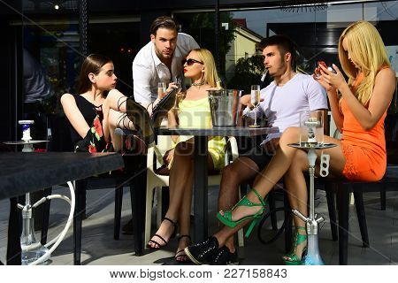 Man Vapor Hookah Pipe In Shisha Bar Lounge. Twins Women And Men Friends Relax In Cafe Outdoor. Celeb