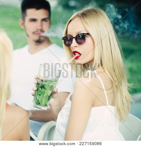 Woman Drink Mojito Cocktail With Man. Man Vaping Hookah Pipe With Girlfriend In Bar. Friends At Shis