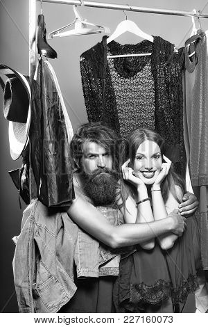 Fashion Couple Denuded Of Brunette Girl And Bearded Man Choose Clothes To Wear Near Rack With Hanger