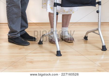 Legs Of A Very Old Woman In White Socks And Slippers. The Old Lady Learns To Walk With The Help Of A