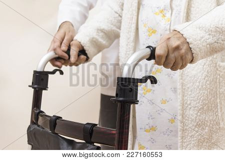 Hands Of A Very Old Woman Hold The Handles Of A Rehabilitation Walker. The Man Nurse Belay And Helps