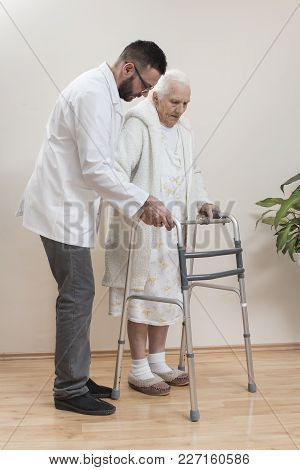 Geriatric Doctor Teaches To Walk An Old Woman Using A Rehabilitation Walker.