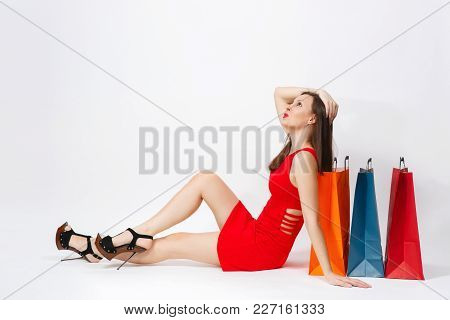 Attractive Glamour Caucasian Fashionable Young Brown-hair Woman In Red Dress Sitting At Multi Colore