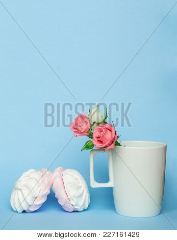 Tea Cup With Rose Flower And Zephyr Marshmallows On Blue Pastel Color Background. Sweet Dessert With