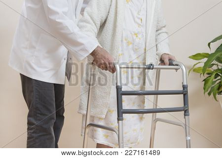 Medical Rehabilitation Balconies. Grandma Learns To Walk With The Help Of A Walker And Assisted By A