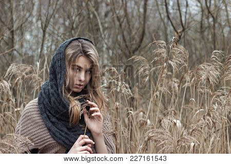Beautiful Sad Girl Is Walking In The Field. Photo In Brown Tones.