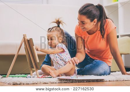 Mother And Daughter In Their Home. Little Girl Is Learning To Draw.
