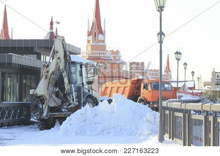 Clearing Snow From The Road With Bulldozer And Truck In The City, Urban Landscape