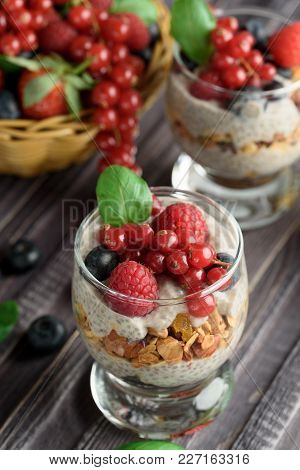 Two Glasses Of Chia Pudding With Fresh Strawberries, Raspberries And Blueberries. Basket With Berrie