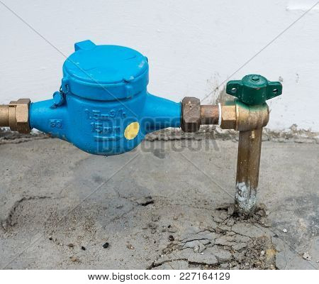 Closeup Of The New Water Meter Near The House Wall In The Urban Area.