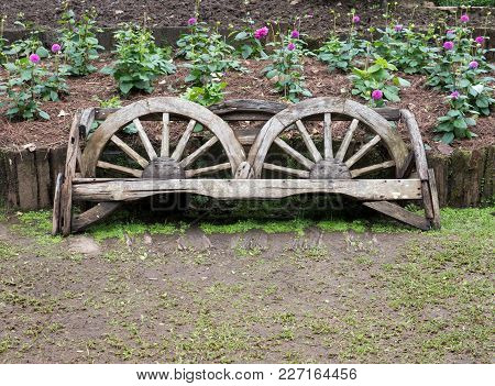 Wooden Bench Which Made From The Old Cart Wheel In The Flower Row Of The Botanical Garden.