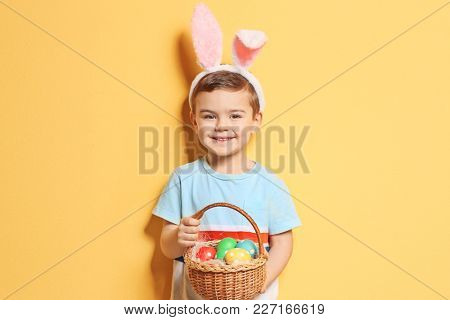 Cute little boy with bunny ears holding basket full of Easter eggs on color background