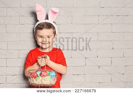 Cute little boy with bunny ears holding basket full of Easter eggs on brick wall background