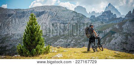 Caucasian Biker On The Mountain Trail. Panoramic Photo. Italian Dolomites.