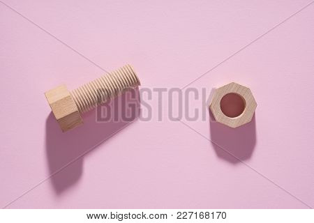 Hex Nut And Bolt On Pink Background. Build And Repair Concept, Pop Art. Wooden Bolt And Nut.