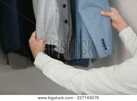Man picking jacket from closet. Fashionable wardrobe