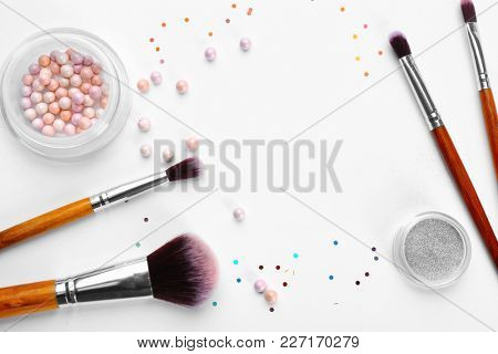 Makeup brushes with cosmetic powder of professional artist on white background