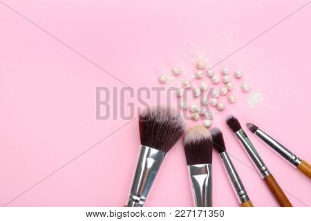 Brushes with facial powder balls of professional makeup artist on color background
