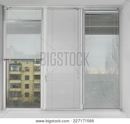 Beautiful urban view from window with venetian blinds