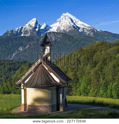 Small Chapel Kirchleitn And Snow-capped Summits Of Watzmann Mountain. Square Stock Photo Captured In