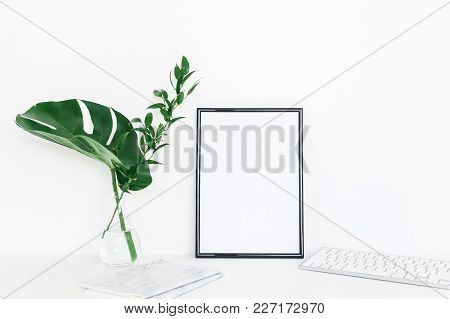 Desk With Photo Frame, Notebook, Computer, Green Leaves. Creative Workspace. Front View, Copy Space,