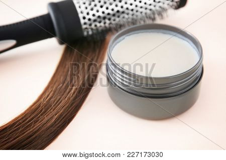 Jar with clay for styling, brush and strand of brown hair on color background
