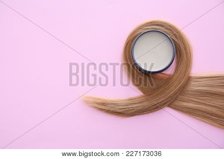 Jar with clay for styling and strand of blonde hair on color background