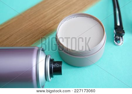 Jar with clay for styling, spray and strand of blonde hair on color background