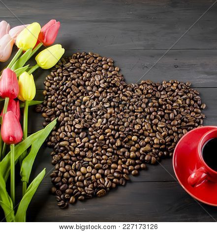 Coffee Cup And Scattered In The Form Of A Heart Of Coffee Grains On Dark Wooden Background. Bouquet
