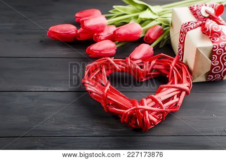 Nice Wicker Red Heart With Gift Box And Red Tulips  Placed On Old Dark Wooden Table. Valentines Day