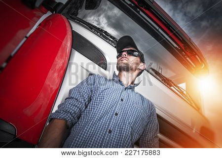 Proud Truck Driver Portrait. Caucasian Driver And His Red Semi Truck. Transportation Industry Theme.