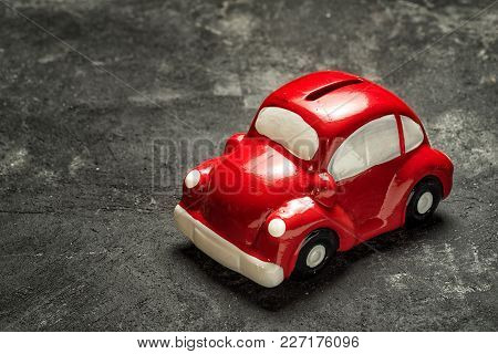 Red Toy Car Model Piggi Money Box On A Black Cement Background With Copy Space, Car Loan Savings Con