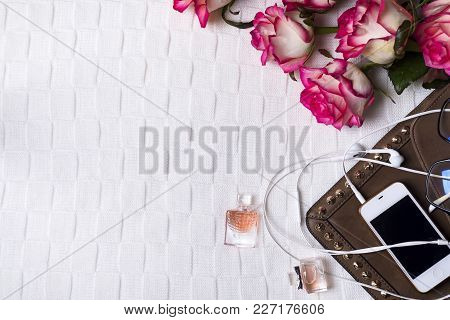 Female Clutch With Phone, Headphones And Perfume Bottles With Flowers On Light Background. Perfumery