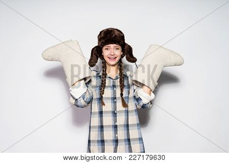 Happy Young Russian Girl In A Hat With Ear-flaps Holds Warm Winter Felt Boots